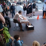A gentleman in Old Town plays the glass harp before a crowd