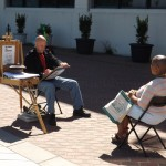 A gentlemen draws a caricature of a lady at the waterfront