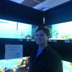 Marketing Specialist Aubrey Nesbitt stands in front of an aquarium