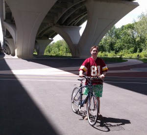 Aubrey Nesbitt takes a break from riding his bicycle below the Woodrow Wilson Bridge
