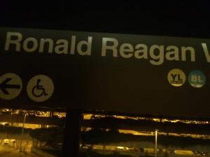 A sign for Reagan near an illuminated parking deck