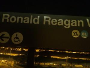 A sign for Reagan near an illuminated parking deck