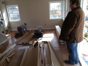 Principal Broker watches as hardwood floors are installed
