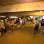 Vendors selling goods in a parking garage basement