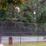 Caged basketball court with bench near mid-rise River Towers condo